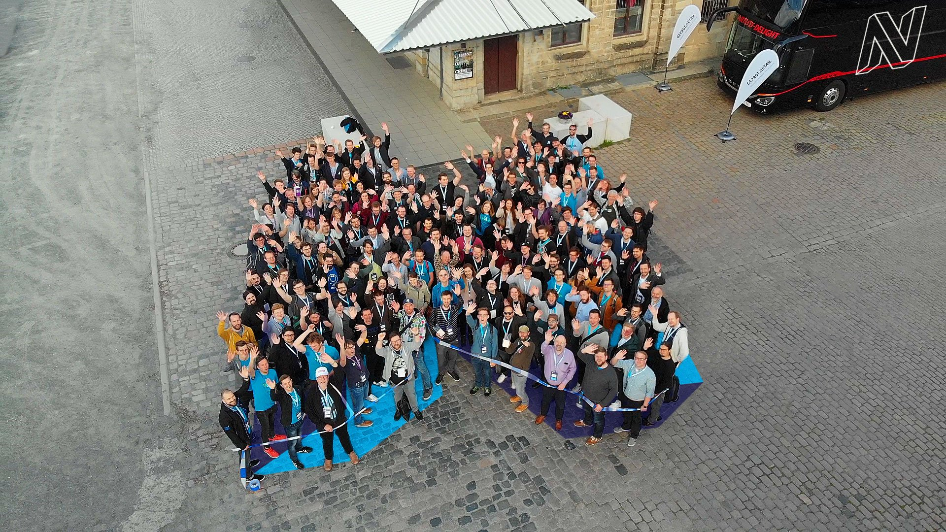 Neos conference attendees form the project logo outside the conference location