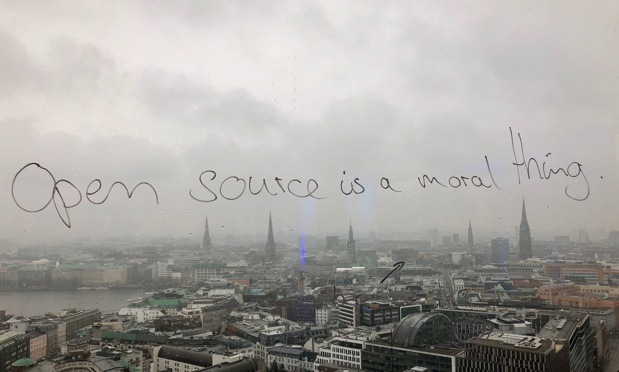 "Skyline of Hamburg, with ""Open source is a moral thing"" written on the window pane."