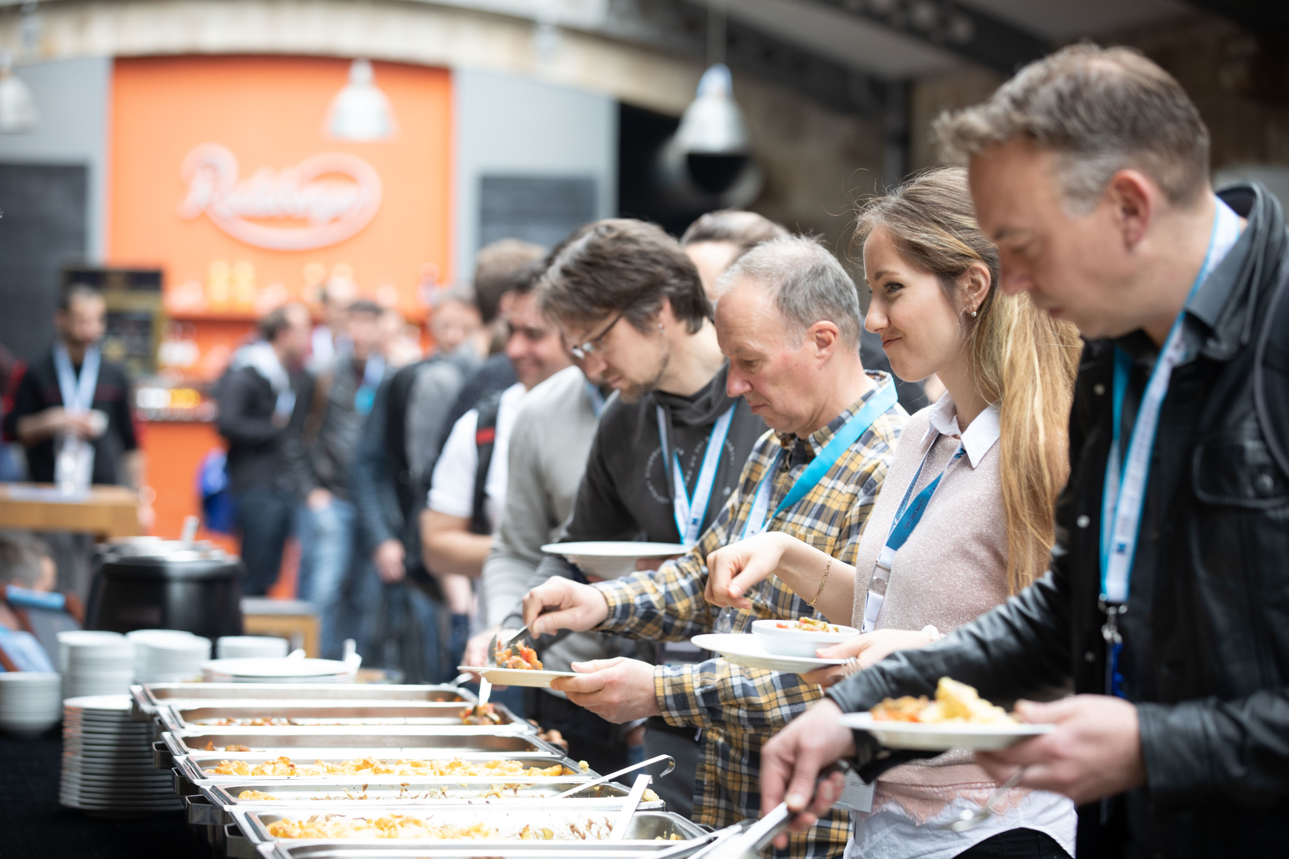 Attendees queuing for food during lunch break